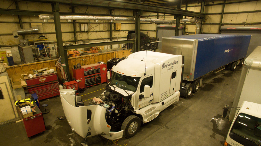 Rowe Transfer, Inc. semi truck with hood open, engine exposed, parked in Rowe warehouse