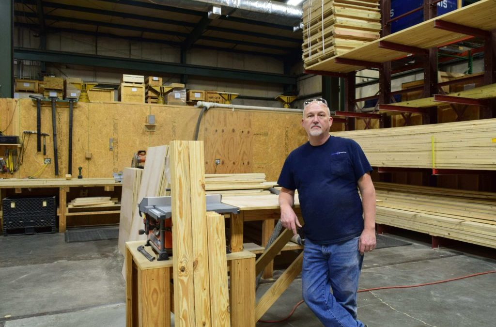Doug West, Rowe Transfer employee, leaning on crating materials